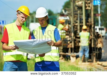 Two engineer site managers builders with blueprint plan at geology roadwork construction site