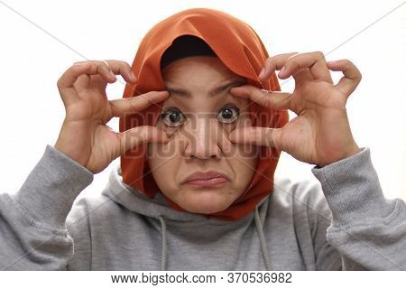 Tired Muslim Woman Open Her Eyes With Finger, Trying To Keep Awake, Close Up Portrait Isolated On Wh
