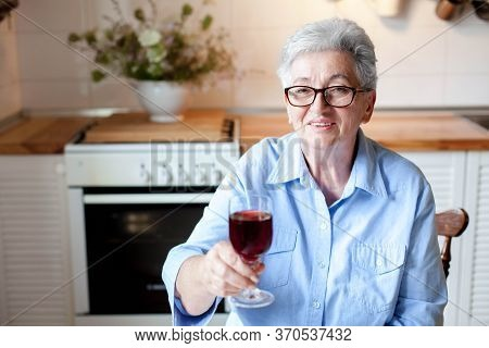 Senior Woman Drinking Red Wine At Home. Grandmother Celebrating Holiday Alone. Retired Person Relaxi