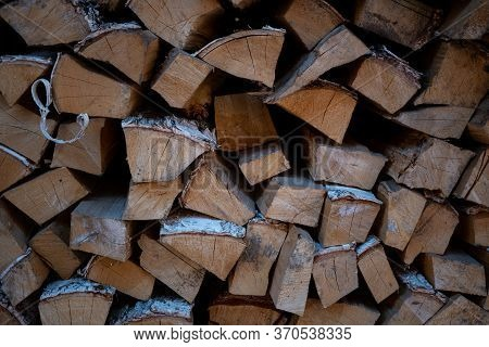 Background Image Of Woodpile. Firewood Is Neatly Stacked. Birch Logs. Firewood For Kindling A Stove.