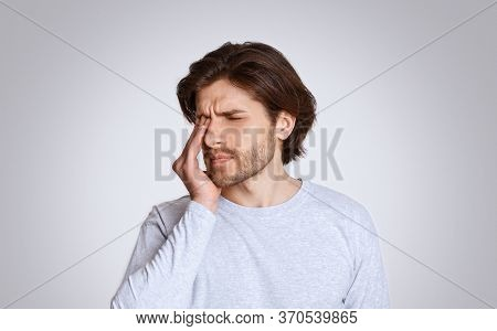 Feeling Unwell. Guy Feels Pain In His Closed Eyes And Presses Hand Isolated On Gray Background, Stud