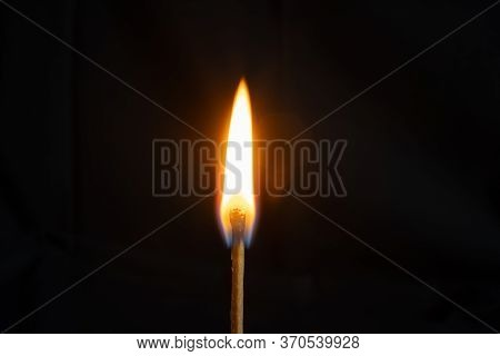 Low Key, Close Up Burning Matchstick On Black Background With Bokeh