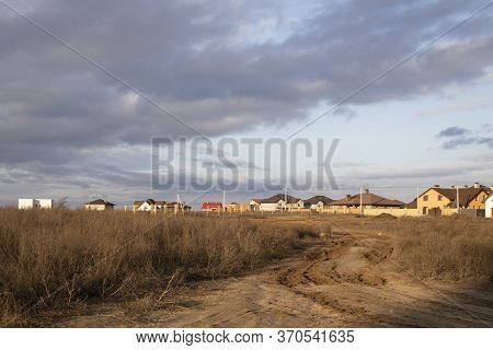 Dirt Roadway To New Cottage Houses. Outland Road View With Houses And Beautiful Sky