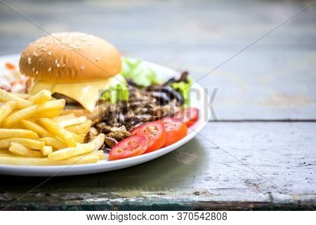 Homemade Hamburger With Beef Or Pork Meat With Lettuce And Cheese, Vegetables, Sauce And French Frie