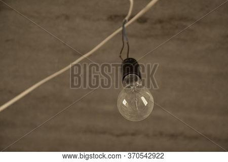 Light Bulb Hanging On Wires On Concrete Ceiling In Unfinished Construction