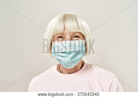 Portrait Of Happy Female Senior Patient Wearing Medical Protective Mask Looking At Camera And Smilin