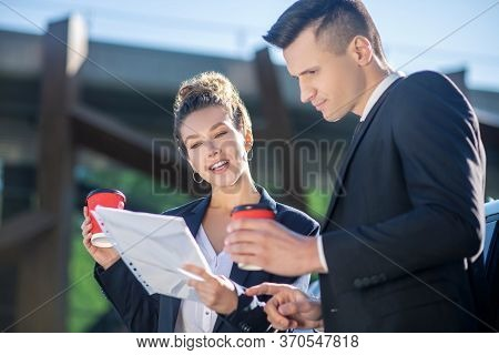 Interested Responsible Man And Woman With Coffee Looking Document