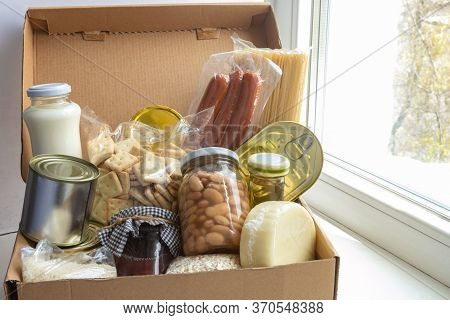 Grocery Set For Needy In Crisis, Pasta, Beans, Canned Food Etc In Cardboard Box On The Windowsill, F