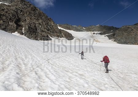 Climbers Team On A Trail Through A Dangerous Glacier And Avalanches In Austiran Alps. Route To The G