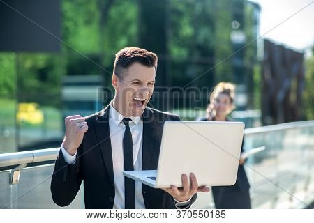 Young Man With A Laptop Enthusiastically Rejoicing