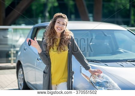 Smiling Woman With Keys Standing Near Gray Car