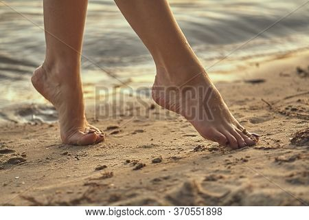 Female Feet Barefoot On A Sandy Beach In The Water. Close-up Of Beautiful Female Legs. Wet Foot.