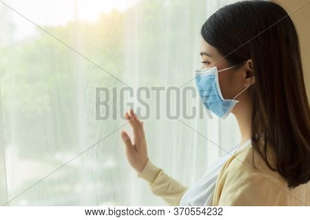 Young Asian Woman In Medical Mask Stay At Home For Self Quarantine. Home Quarantine, Prevention Covi