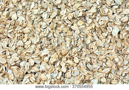 Pile Of Oat-flakes, Background Of Uncooked Oats. Texture Of Raw Oatmeal. Diet Food Concept