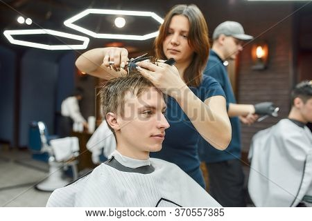 Focused Barber Girl Holding Scissors And Comb In Hands And Making Haircut For Her Client. Young Guy