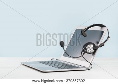 Laptop With Blank Screen And Headphones On Desk Blue Background. Copy Space. Distant Learning Or Wor