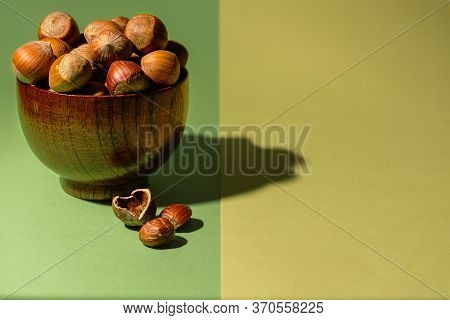 Bowl Of Raw Hazelnuts Next To An Hazelnut Without Its Shell On A Green And Yellow Background