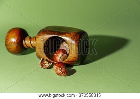 Peeled Hazelnut Next To Its Shells And A Nutcracker, On Green Background