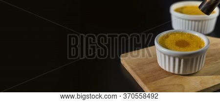 Close Up Homemade Creme Brulee In White Ramekin  With Sugar Burn Top Up On Black Background With Cop