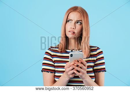 Image of perplexed charming girl in striped t-shirt using mobile phone isolated over blue background