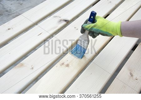 Woman Hand With A Brush Varnishes Old Wooden Boards. Paint Brush Preparation To Stain The Wood Slats