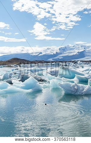 Natural Wonder Of Iceland. Amazing View Of Icebergs And Ice Floes Floating In A Large Jokulsarlon Gl