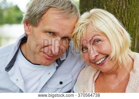 Old man and old woman smile as a couple of seniors outdoors