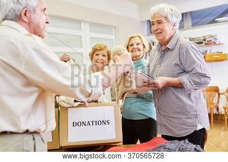 Seniors as volunteers collect clothing donation for the needy in the clothing store