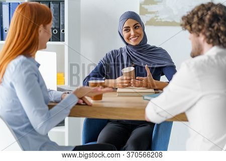 Muslim Woman Telling A Joke To Her Co-workers During A Coffee Break