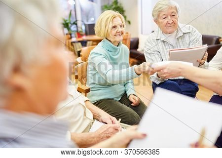 Seniors with a doctor in group therapy or painting therapy in a retirement home