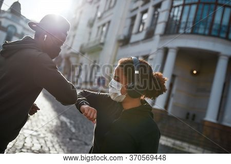Keep Distance. Young African Couple Of Runners In Medical Protective Masks Bumping Elbows Instead Of