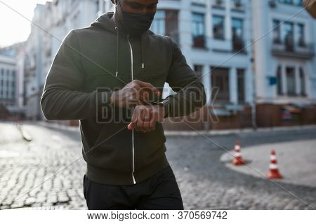 Getting Ready To Run. Young African Male Runner In Black Sportswear And Medical Protective Mask Touc