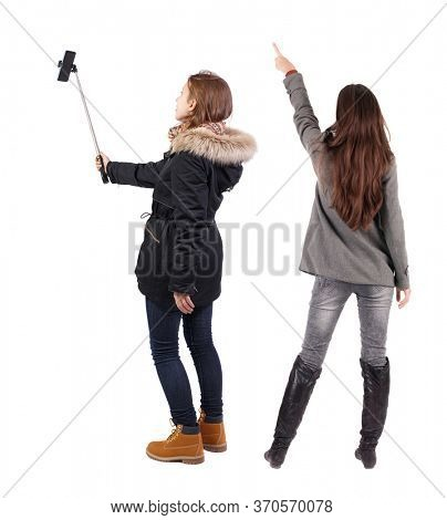 Back view of two young woman photographed on a mobile phone in winter jacket. Rear view people collection. backside view of person. Rear view. Isolated over white background.