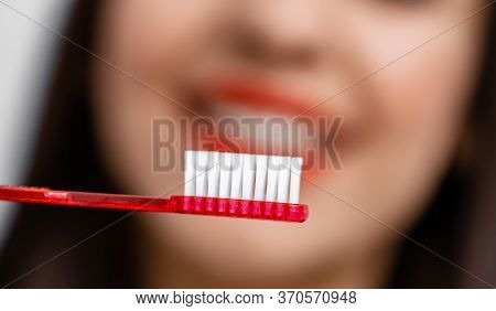 Woman With Great Teeth Holding Tooth-brush In Front Of Camera. Blurred Background.