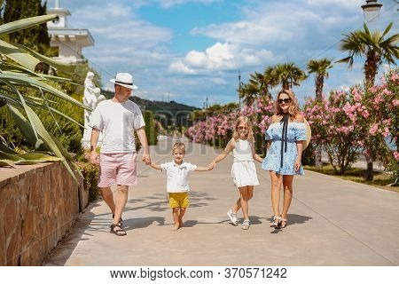 Adult Man And Woman With Little Boy And Girl All Holding Hands And Enjoying Summer Vacation Walking