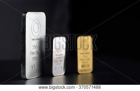 Gold And Silver Bars Of Different Weights On A Dark Background. Selective Focus.