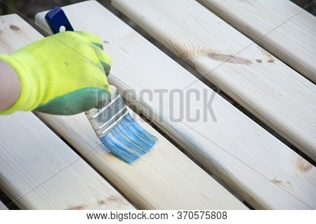 Woman Hand In Glove With A Brush Varnishes Old Wooden Boards. Worker Paint With Brush A Wood Table F