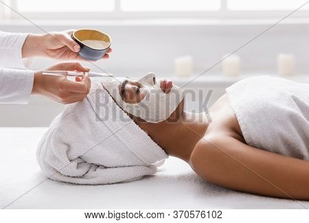 Young African American Lady Getting Facial Treatment At Spa, Therapist Applying Clay Mask On Woman F