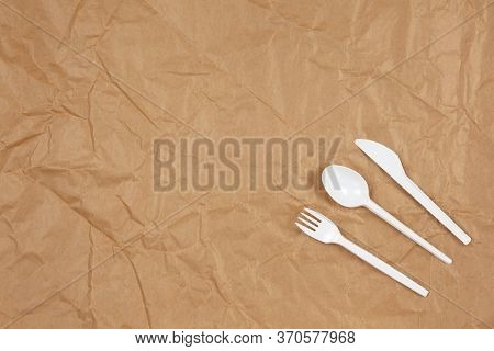Reusable Recyclable White Fork, Spoon, Knife Made From Corn Starch On Brown Crumpled Craft Paper, Co