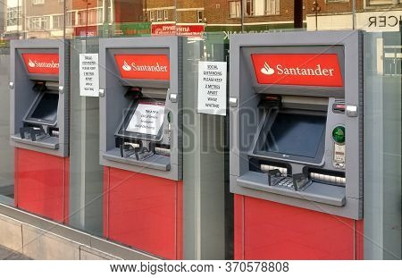 London, United Kingdom - April 09, 2020: Three Santander Bank Atm Withdrawal Terminals With Middle O