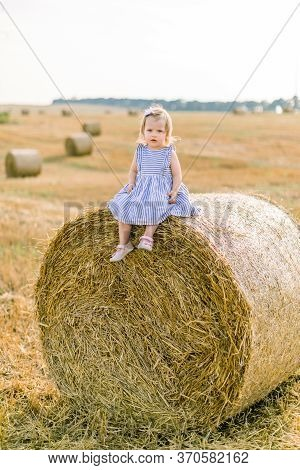 Full Length Portrait Of Cute Pretty Little Baby Girl In Striped Dress Sitting On Hay Stack Or Bale O