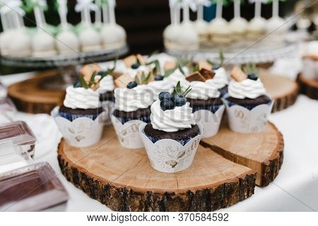 Chocolate Cupcakes Decorated With Cream And Berries On The Wooden Plate.wedding Cupcakes