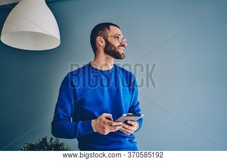Cheerful Young Bearded Caucasian Hipster Guy Enjoying Modern Digital Tablet For Work And Education
