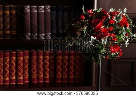 Old Books On An Archival Shelf Of Library Of Storehouse. Two Rows Of Books And Red Flowers