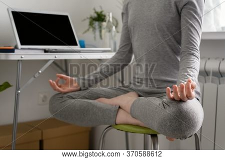 Teenager Girl Is Training At Home, Doing Yoga Exercises, Sitting In Lotus Position, Meditation. Remo