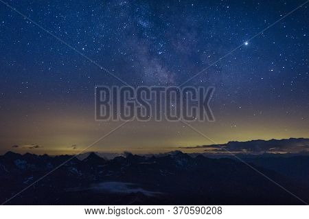 The Milky Way In The Night Sky Over The Austrian Alps. View From The Way To Grossglockner Rock Summi