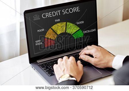 Credit Score Concept, A Man Looking At A Laptop Checks His Credit History