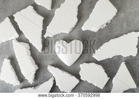 White Polystyrene Heart On A Gray Background, Surrounded By Fragments Of Polystyrene. Shards Of A He