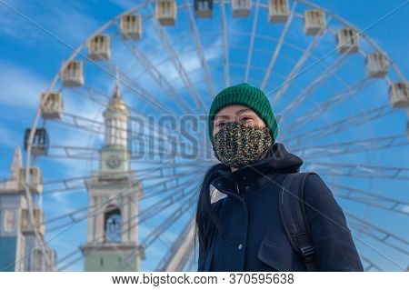 Kiev, Ukraine - March 26, 2020: Ferris Wheel On A Background Of Blue Sky And A Girl In A Protective