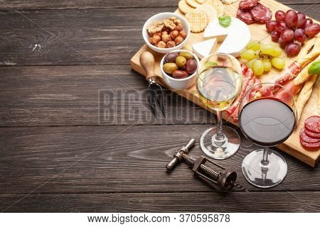 Cheese, meat, grapes and olives antipasto. Appetizer selection plate and glasses with red and white wine. With copy space